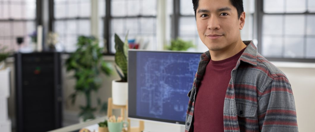 man in charge of edge computing standing in front of computer monitor