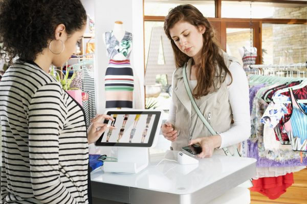 woman making a mobile purchase in a clothing store